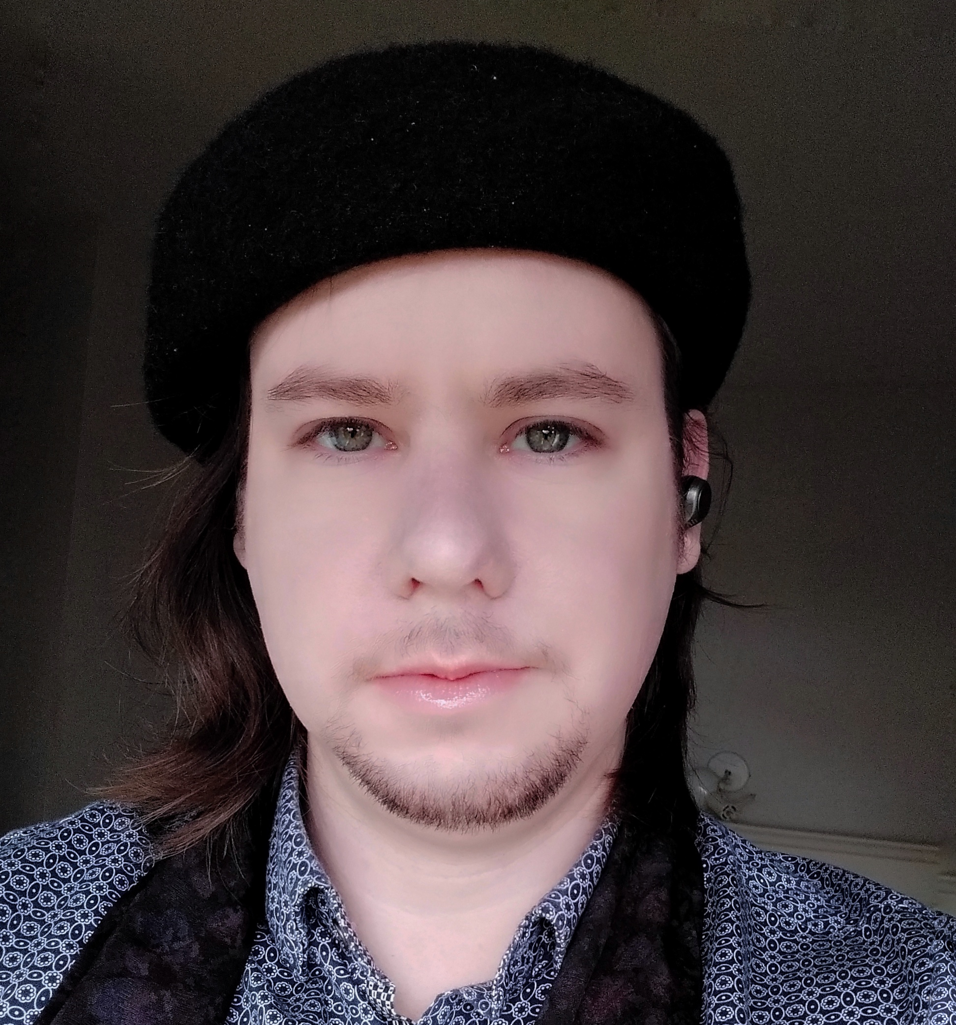 A Photo of S. Jonathon O'Donnell, wearing a black beret and purple scarf.